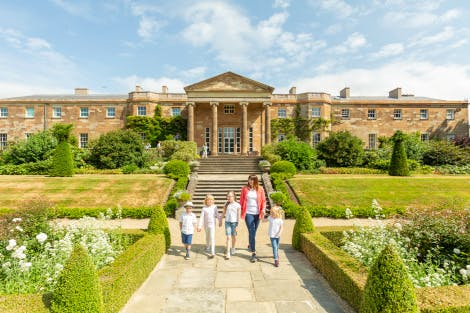 A lady and four young children walk down stone steps on the South Terrace towards the Jubilee Parterre. The South Façade of the Hillsborough Castle is visible in the background and a blue sky hangs above. The sun is shining brightly and highlights the nearby box-trimmed hedges and white flowers.