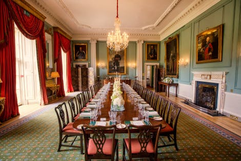 Photo taken from the end of the State Dining Room table to the end. Table in dressed with silver cutlery, crockery and crystal.