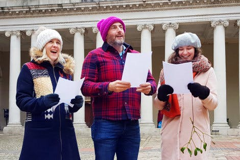 Group of carol singers singing in front of the colonnade in Clock Court at Hampton Court Palace