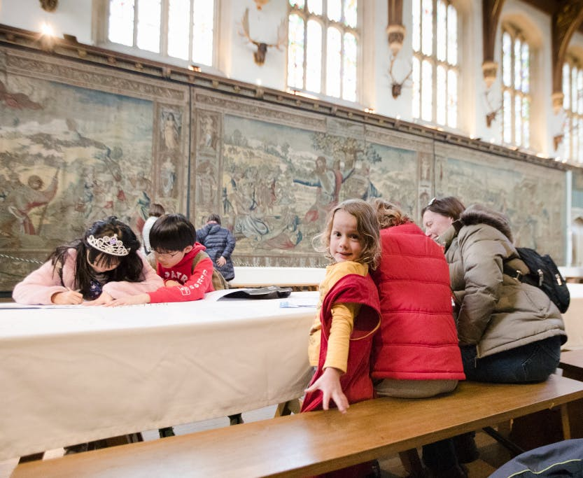 Visitors with children sitting at a long table in the Great Hall working on family activities.