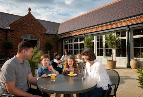 A family of a mother, dad and two children in the cafe courtyard of the Weston Pavilion (visitor centre) at Hillsborough Castle and Gardens