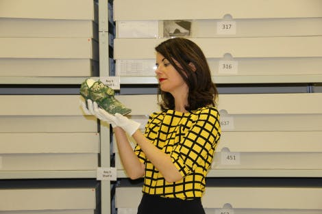 Deirdre Murphy, Senior Curator, holds a shoe in the objects stores at Kensington Palace