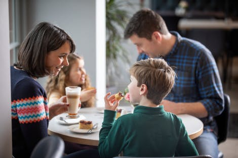 A family of two adults and two children enjoy food in the Stableyard Tea Room at Hillsborough Castle and Gardens.