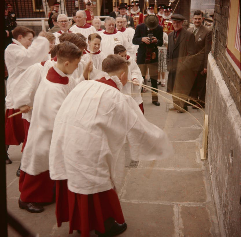 The ceremony of Beating the Bounds. Choirboys beating one of the boundary stones with willow wands