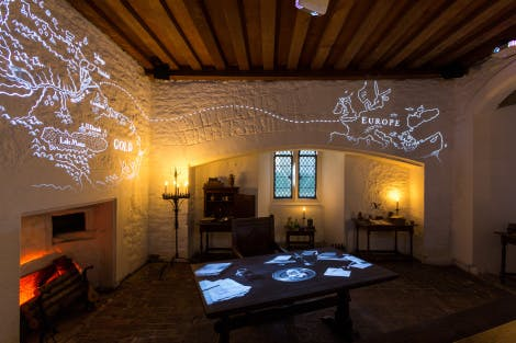 Sir Walter Raleigh's Study downstairs in the Bloody Tower at the Tower of London, showing a desk and walls with projections.