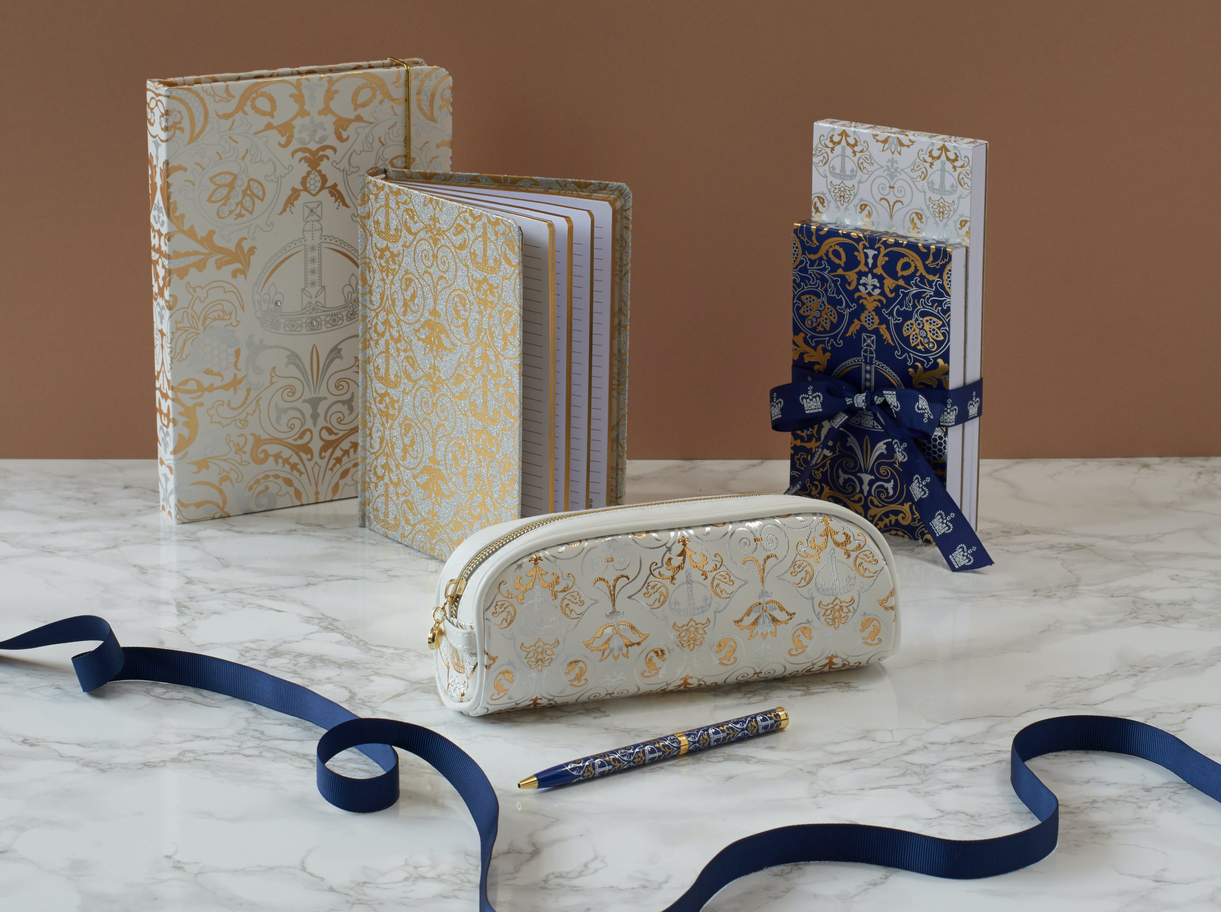 A collection of stationery items under the Royal Victoria range shown left to right: Royal Victoria white A5 luxury notebook, Royal Victoria Royal Victoria B6 glitter gold and silver notebook, Royal Victoria Luxury White Pencil Case, Royal Victoria navy gem pen, Royal Victoria list notepads set of two