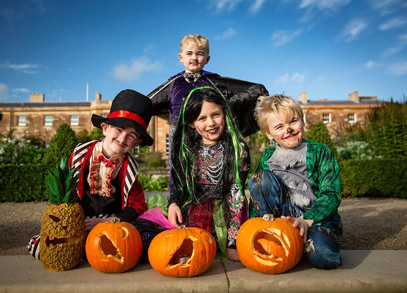 Children in Halloween costumes outside Hillsborough Castle posing with pumpkins.