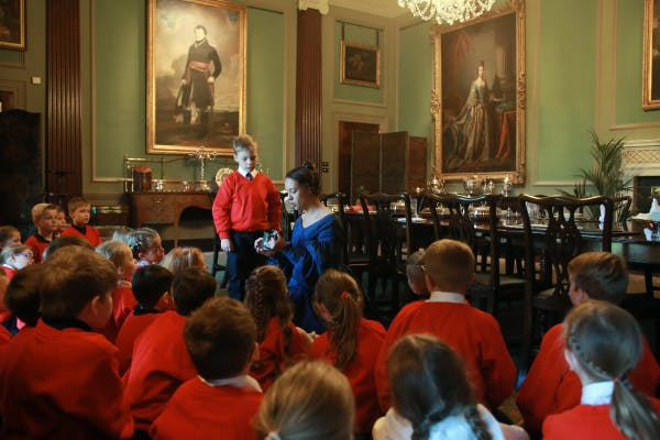 Primary school students listen to a costumed presenter during a school session at Hillsborough Castle and Gardens