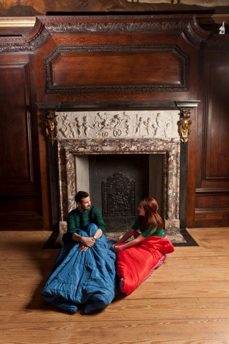 Two people sit in sleeping bags on the floor of a historic room in Hampton Court Palace, in front of a fireplace