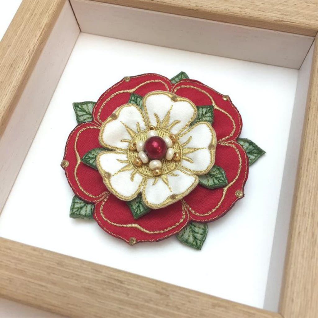 Embroidered and hand painted Tudor rose, displayed in a wooden frame.