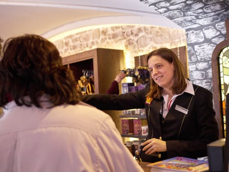A female staff member in their uniform stands behind a till and serves a female customer.