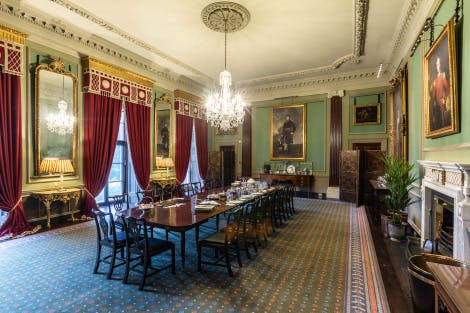 A large Georgian-style dining room with a table dressed for dinner in the middle. The walls are covered in pale mint green decor and there are paintings covering the walls