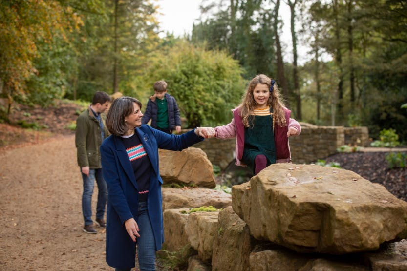 A family walk through the Lost Garden at Hillsborough Castle and Gardens in autumn 2019. The children are walking on the boulders on either side of the path, surrounded by orange and yellow autumn foliage in the background.