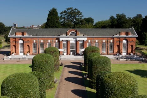 The Orangery at Kensington Palace surrounded by the gardens. The Orangery was previously used as to house plants in the winter months but is now used a restaurant and wedding venue.