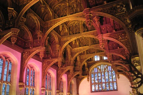 The Tudor hammerbeam ceiling of Hampton Court Palace's Great Hall shown with pink lighting