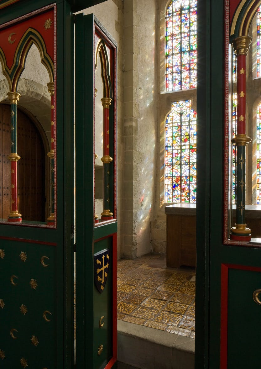 A photograph featuring the painted timber screen and stained-glass window of The King's Private Chapel at The Wakefield Tower Throne Room at the Tower of London.