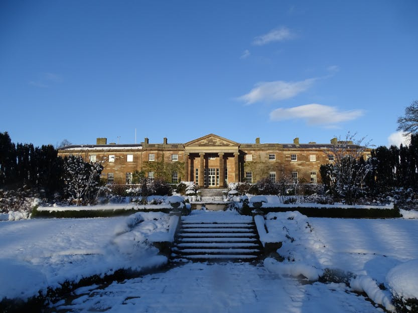 Hillsborough Castle's South façade basked in sunlight and surrounded by gardens laden with heavy, fresh snow. A blue, cloudless sky above reflects blue hues across the snow in stark contrast to the yellow lit stone of the castle.