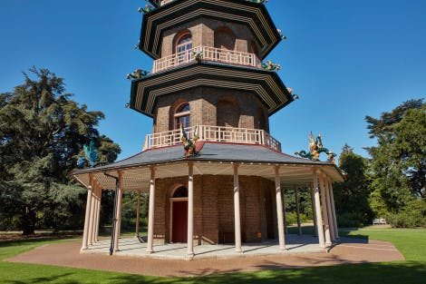 The ground gloor of the Great Pagoda at Kew Gardens, under a bright blue sky and surrounded by trees