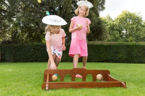 Two young girls dressed in pink play with a garden game on the garden grounds at Kew Palace