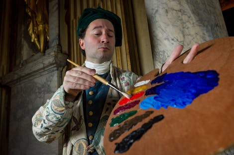 An artist character stood painting in Kensington Palace