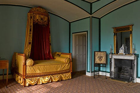 Princess Elizabeth's bed alcove with a reconstruction of her bed in gold and red fabric, in her bedroom at Kew Palace