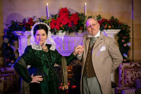 Costumed interpreters pose in front of a grand fireplace decorated with Christmas foliage at Hillsborough Castle