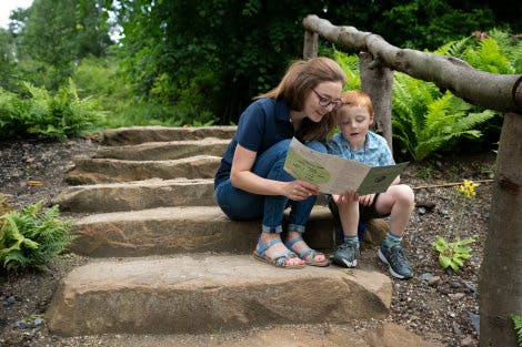 Parent and child sitting looking at a garden trail