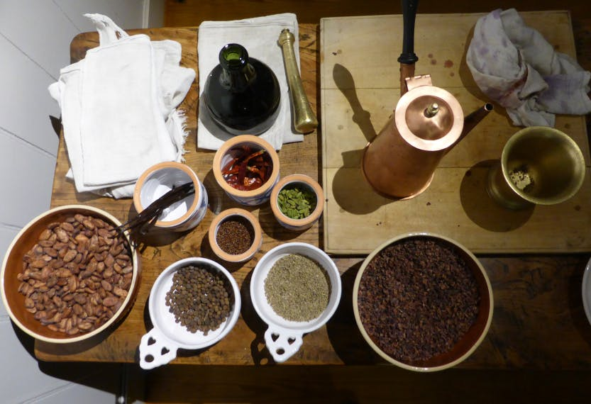 Chocolate Kitchen demonstration set-up with chocolate pot and various ingredients including cocoa beans and chillies.