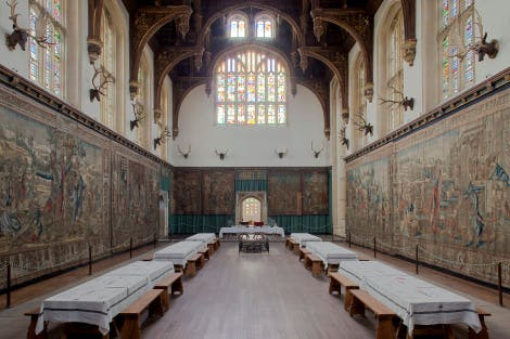 The Great Hall with its hammber-beam roof, looking east, with two long tables on either side and the Abraham tapestries hanging from underneath the windows