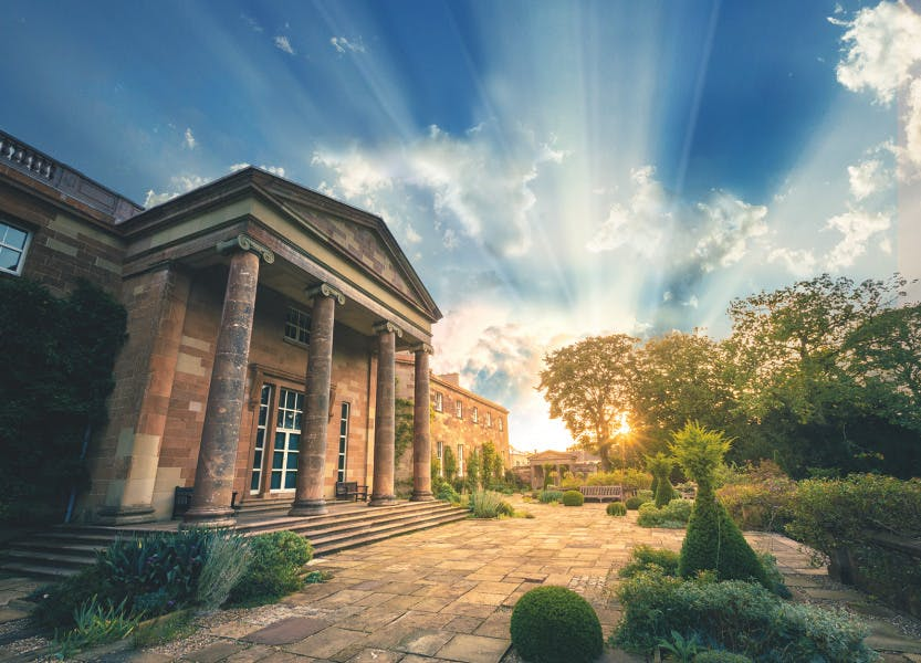 Hillsborough Castle on a bright morning at sunrise. The gardens show in the background as the sun rises over the trees on a bright, partially cloudy blue sky