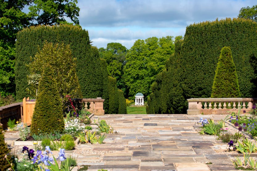 Hillsborough Castle Gardens, looking towards Yew Tree Walk and Lady Alice's Temple. An area paved with flagstones and set with flowerbeds featuring irises and other plants is in the foreground.