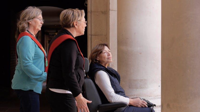 Two female volunteers are standing behind a female volunteer in a wheelchair.