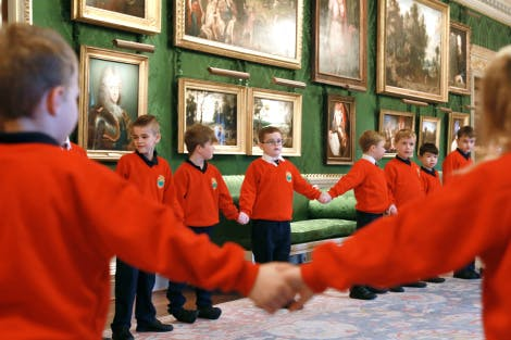 School children take part in a learning activity in the throne room at Hillsborough Castle. They are holding hands in a circle.