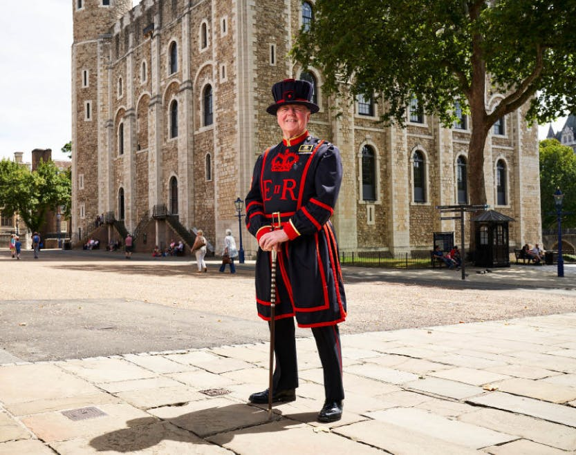 Yeoman Warder Pete McGowran standing in front of the White Tower on a sunny day.