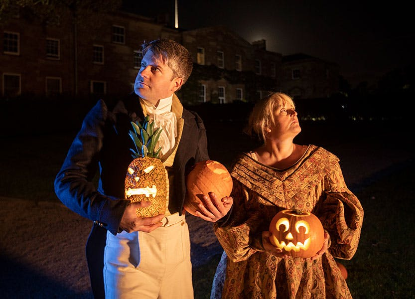 Two actors pose with pumpkins at night in the gardens of Hillsborough Castle and Gardens in period dress.