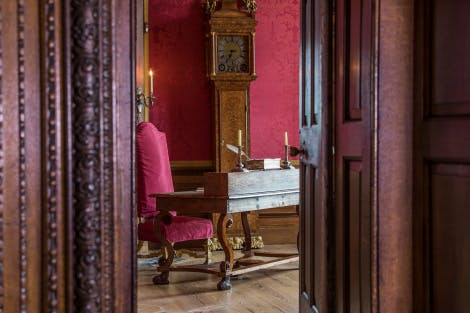 The King's Closet, looking south-east through the entrance doorway. Showing a floor standing clock (grandfather clock) with an oak case veneered with burr walnut (c1695) by Daniel Quare (1649?-1724), a walnut veneered writing table (c1680) and a gilt high-backed Colville chair (1689-94) upholstered in red silk velvet.
