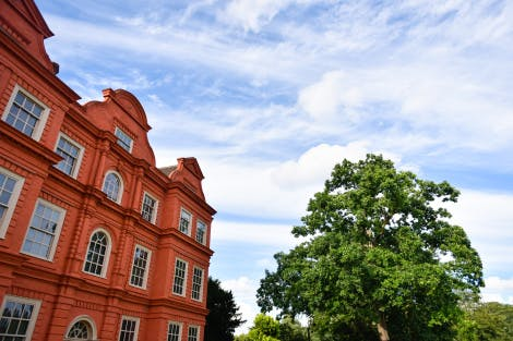 Kew Palace under a blue cloudy sky with a green tree in the background