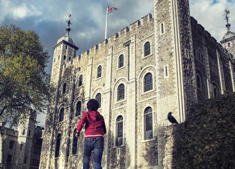 Boy runs towards the White Tower at the Tower of London.