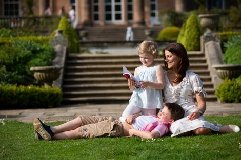 A woman and her two children enjoy the Jubilee Parterre and South Lawn at Hillsborough Castle and Gardens. The caste is shown in the background