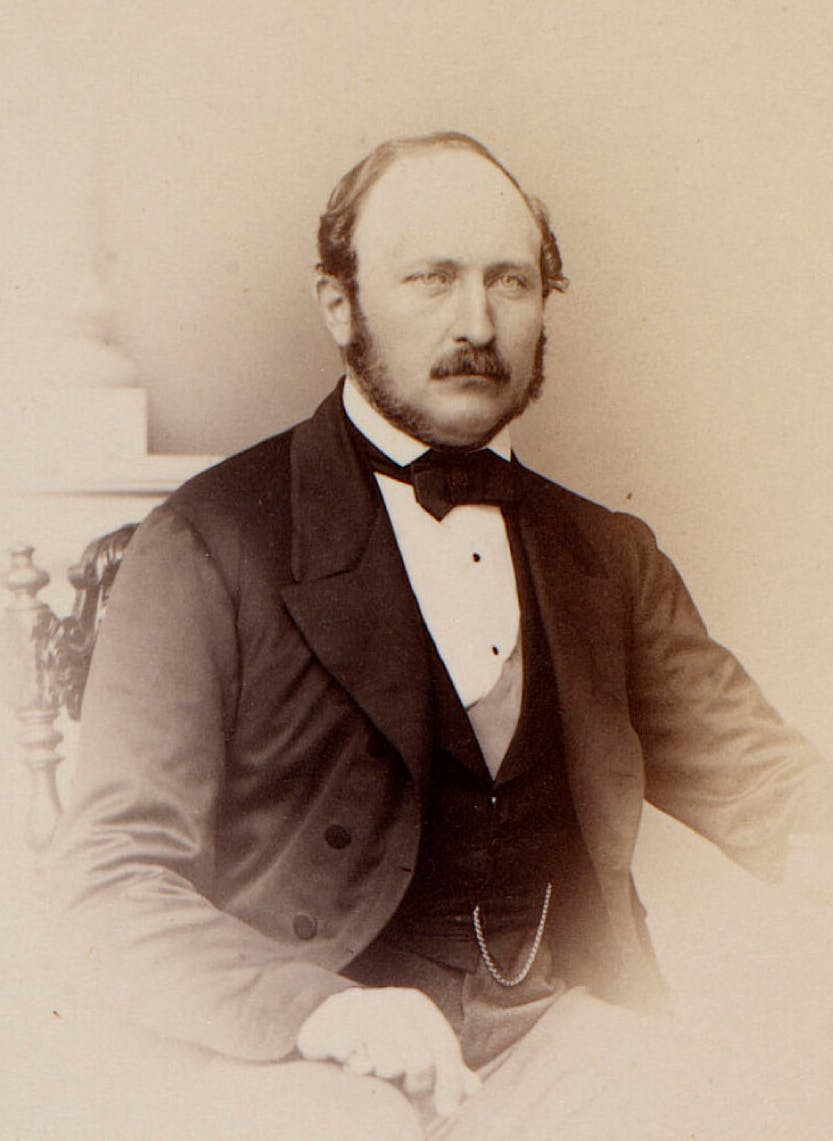 Photograph of a half length portrait of Prince Albert, seated in a chair, facing towards the camera. He poses with his right hand in his lap.