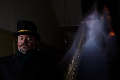 A ghost tour guide stands on the Silverstick Stairs of Hampton Court Palace at night. A ghost representing Jane Seymour appears behind him.
