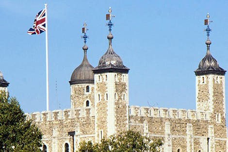 The top of the White Tower at the Tower of London with its Union Jack flag flying.