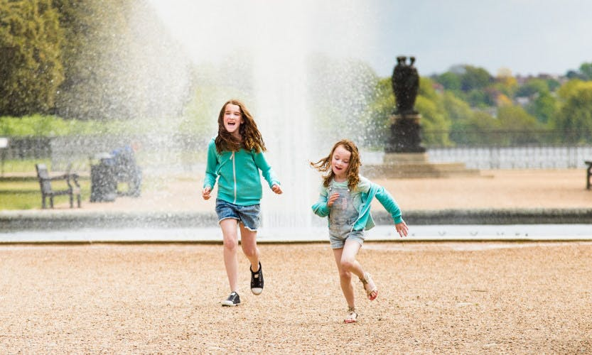 Two female children playing next to the fountain in the gardens of Hampton Court Palace.