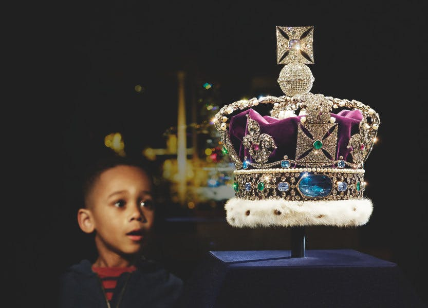 Boy looks at the Imperial State Crown on a dark background