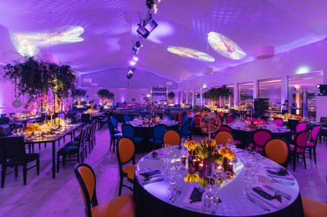 Dinner tables set up in an events venue flooded with purple light and decorated with orange trees