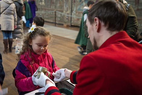 Photo of a little girl exploring historical objects with the help of a male member of staff at Hampton Court Palace