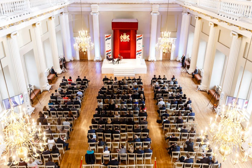The baroque main hall of the Banqueting House laid out as a theatre-style event with the red chair of state at the far end