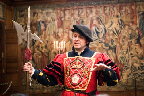 A Live Interpreter dressed as a Tudor Yeoman of the Guard, wearing a red livery coat with HR and Tudor Rose, and holding a halberd.
