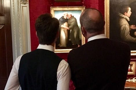 Two visitors with their backs to the camera look at a painting of two saints embracing.