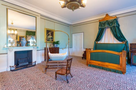 A pale green Victorian bedroom with a large bed and fireplace at Kensington Palace, where Queen Victoria was born